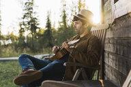 Young man sitting on veranda of a wood house, playing the ukulele - KKAF02180