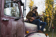 Young amn sitting on a broken truck, playing the ukulele - KKAF02183