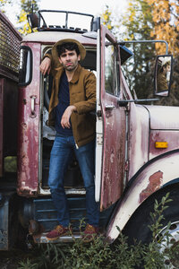 Cool young man standing in cabin of a broken truck - KKAF02186