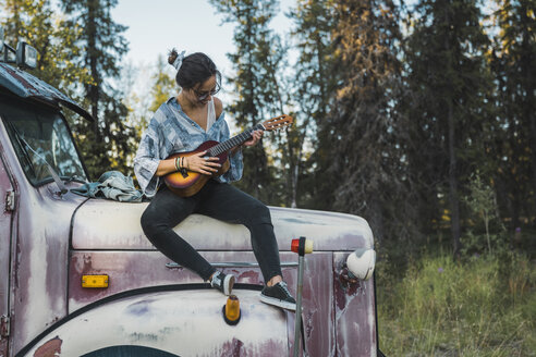 Young woman sitting on a broken truck, playing the ukulele - KKAF02192