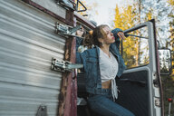 Young woman posing on broken vintage truck - KKAF02195