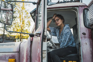 Young woman sitting in cabin of a broken vintage truck - KKAF02198
