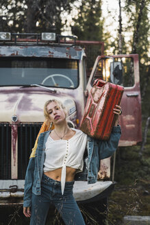 Young woman posing at a broken vintage truck, holding petrol can - KKAF02201