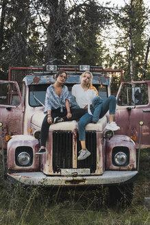 Two friends sitting on a broken truck - KKAF02204