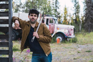 Young man holding axe, standing in front of a broken truck - KKAF02210