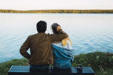 Young couple sitting on a bench, looking at the lake - KKAF02213