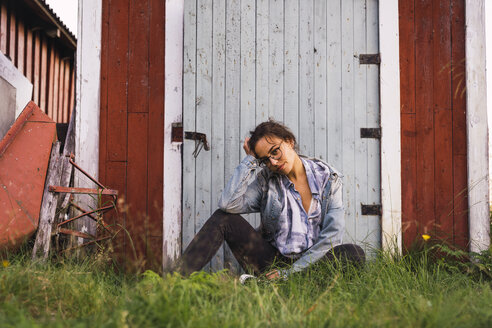 Portrait of a young woman sitting in grass in front of a wooden shack - KKAF02219