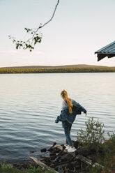 Young woman at a lake, balancing on a plank - KKAF02222