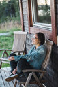 Happy young woman sitting on veranda of a wooden house - KKAF02225