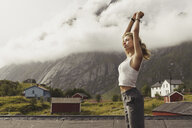 Young woman standing in nature, stretching, Lapland, Norway - KKAF02237