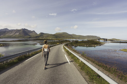 Young woman walking on an empty road, Lapland, Norway - KKAF02240