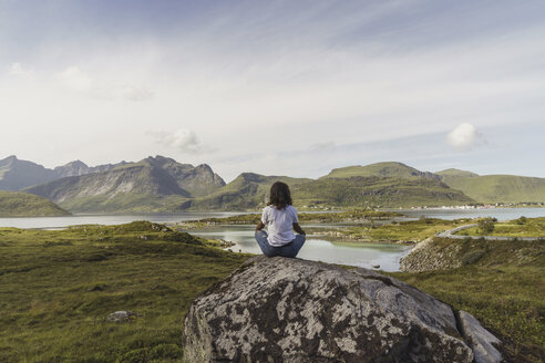 Young woman sitting on a rock, looking at view, meditating, Lapland, Norway - KKAF02243