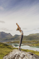 Young woman standing in nature, stretching, Lapland, Norway - KKAF02252