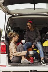 Friends sitting in a camper, taking a break, drinking coffee - KKAF02261