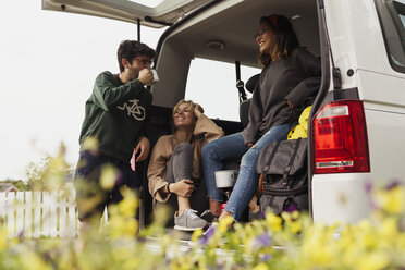 Friends sitting in a camper, taking a break, drinking coffee - KKAF02264