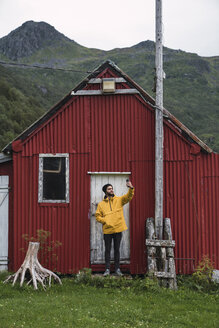 Young man standing in front of corrugated iron shack, taking selfie - KKAF02267