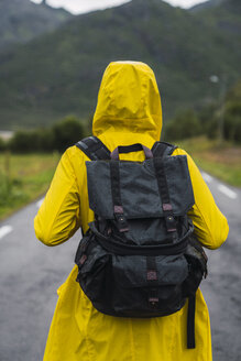 Norway, Lapland, Vesteralen Islands, Young man walking on empty road, rear view - KKAF02273
