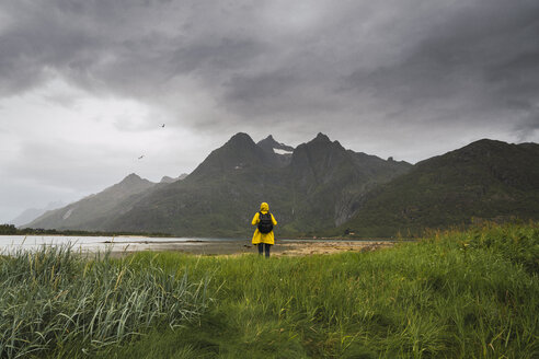 Young man standing at a lake in Vesteralen Island, Lapland, Norway - KKAF02276