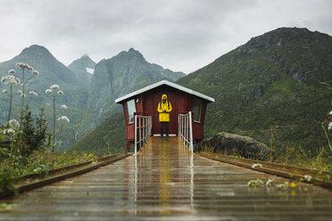 Man in yellow rain jacket waiting at red wood shack, Lapland, Norway - KKAF02279