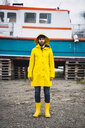 Young man standing in front of a ship, wearing rain clothes, Lapland, Norway - KKAF02282
