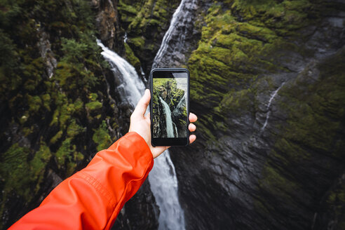 Person taking smartphone picture of a waterfall, Lapland, Norway - KKAF02285