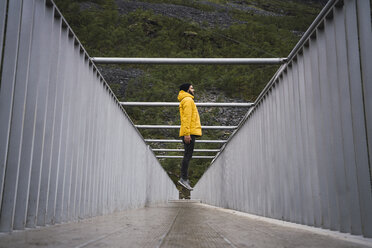 Young man with a rain coat, jumping on a bridge - KKAF02288