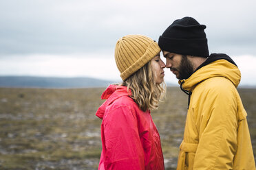 Young couple rubbing affectionately noses, Lapland, Norway - KKAF02300