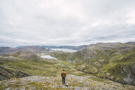 Finland, Lapland, man standing on a hill in stunning landscape - KKAF02312