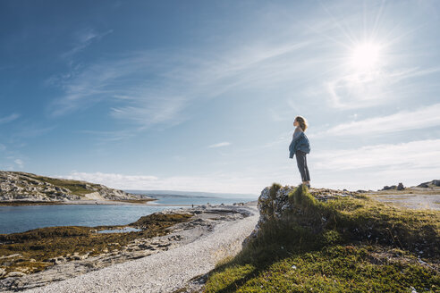 Finland, Lapland, woman standing at the coast in backlight - KKAF02315