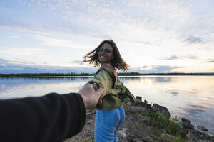 Finland, Lapland, happy young woman holding man's hand at the lakeside at twilight - KKAF02321