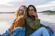 Finland, Lapland, two young women sitting back to back at the lakeside at twilight - KKAF02327