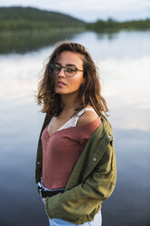 Finland, Lapland, portrait of beautiful young woman at the lakeside - KKAF02330