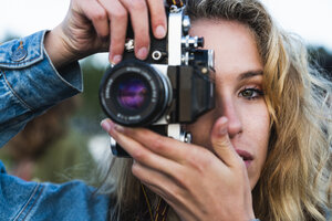 Close-up of beautiful blond young woman taking a picture with a camera - KKAF02336
