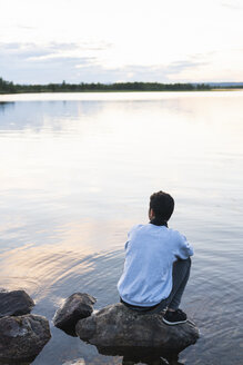 Finland, Lapland, man sitting on a rock in a lake - KKAF02339