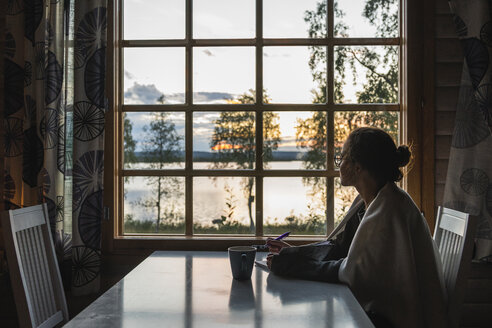 Finland, Lapland, young woman sitting at the window looking at a lake - KKAF02342