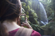 Spain, Canary Islands, La Palma, woman taking a cell phone picture of a waterfall in a forest - PACF00167