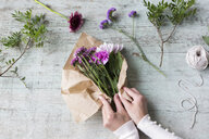Hands of woman wrapping bunch of flowers - JUNF01336