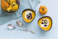 Two bowls of homemade Hokkaido pumpkin soup garnished with cream, pumpkin seed oil and pumpkin seed - JUNF01354