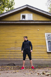 Athlete standing in front of a yellow wood house - KKAF02351