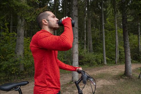 Athlete mountainbiking in nature, taking a break, drinking water - KKAF02369