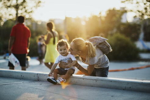 Happy mother with her little son on a square at sunset - AZOF00067