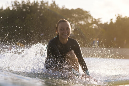 Young woman smiling at camera while surfing near coast, Kuta, Bali, Indonesia - AURF07619
