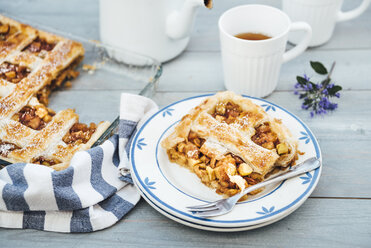 Piece of homemade apple tart on plate and cup of tea - IPF00486