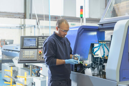 Engineer inspecting part for automatic lathe in engineering factory - CUF43851