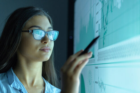 Businesswoman studying graphs on an interactive screen in business meeting - CUF43884