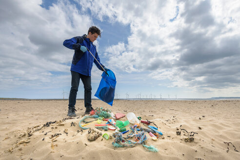 Man picking up plastic pollution collected on beach, North East England, UK - CUF43905