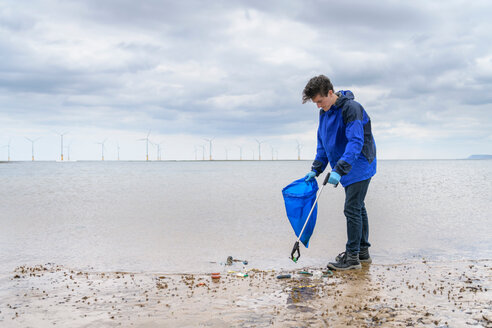 Man using litter picker to remove plastic pollution collected on beach, North East England, UK - CUF43908
