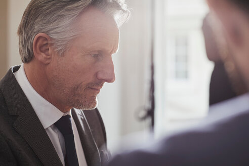 Businessman in office talking to colleague - CUF44031