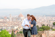 Young couple smiling at mobile phone, Santa Maria del Fiore in background, Florence, Toscana, Italy - CUF44088
