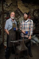 Senior blacksmith and son taking a break in blacksmiths shop, portrait - CUF44124
